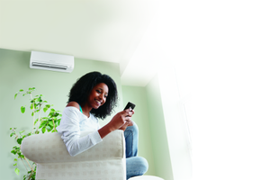 woman on phone with AC unit installed in background Atlas Heating and Air Conditioning Inc HVAC contractor Augusta GA